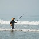 Balinese fisherman in the surf by Michael Brewer