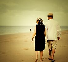Couple walking down the beach by growtograph