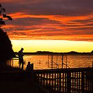 A couple watch the sunset at Strahan, Tasmania by Elana Bailey