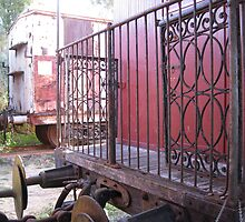 Wrought iron veranda and couplings of train. by Marilyn Baldey