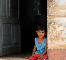 Cuban boy sitting on door step, Trinidad, Cuba by buttonpresser