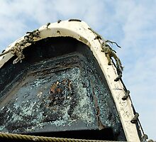 Old boat upright against cloudy Blue sky by buttonpresser