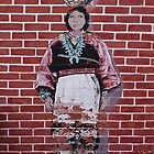 Indian woman painting on a brick building by al holliday