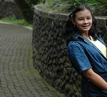 little girl stand up beside the rock wall by bayu harsa