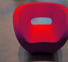 Red Fabric Chair On Grey Cement Floor by JCBimages