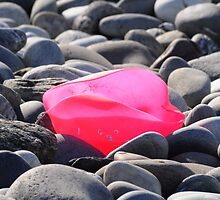 Pink plastic rose on pebble beach by Karin  Funke