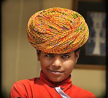 smirking blue-eyed boy in yellow turban, Rajasthan, India by Catherine Ames