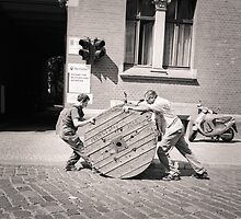 Berlin: Men moving large wooden spool of Cable by Ron Greer