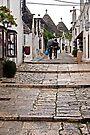Shopping in the Rain - Alberobello Italy by Debbie Pinard